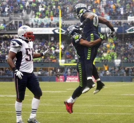 Seattle Seahawks' Braylon Edwards, right, celebrates with Seahawks' Golden Tate as New England Patriots' Jerod Mayo looks on at left, after Edwards caught a pass for a touchdown in the second half of an NFL football game, Sunday, Oct. 14, 2012, in Seattle. (AP Photo/John Froschauer)